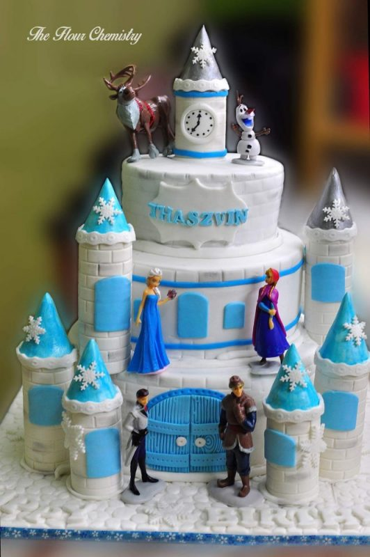 Four-tier Frozen cake with towers and toppers. By The Flour Chemistry