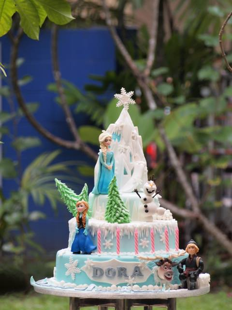 Three tier frozen cake with Elsa, Anna, Olaf, Sven and Kristoff. Made by Just Heavenly