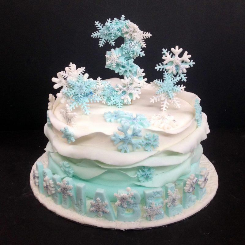 Frozen-themed ruffle cake with snowflake design toppers