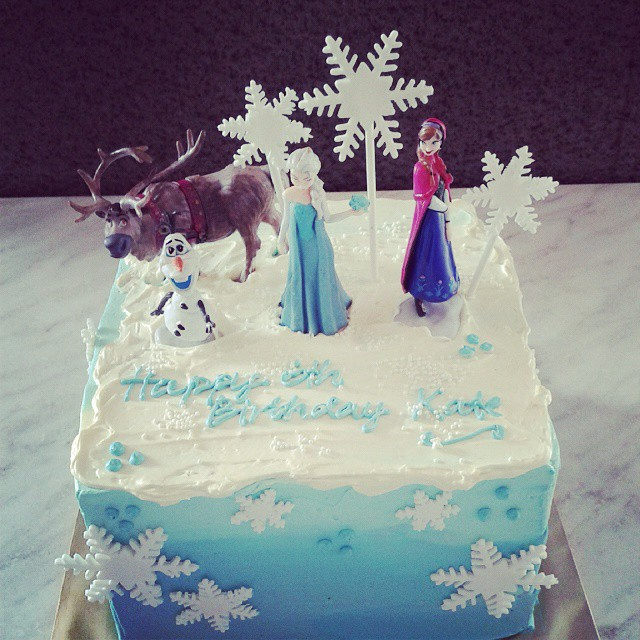 Snowflake themed cake with Frozen toppers Sven, Olaf, Elsa, Anna. Made by Little Collins Cafe. Source