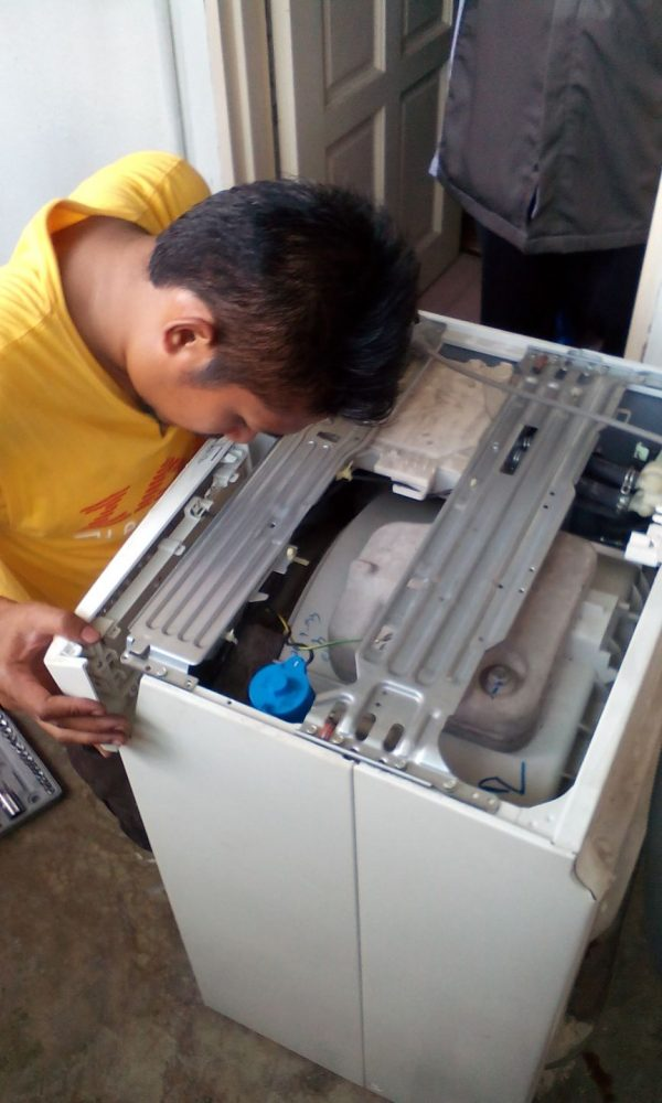 Repairing washing machine by Zam Handyman. Source.