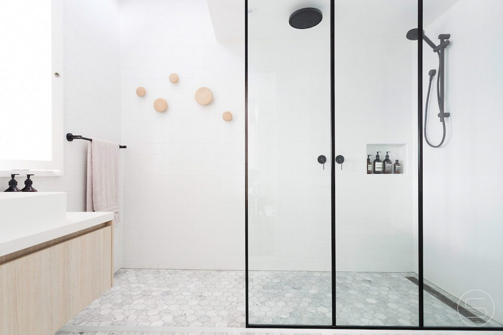 White bathroom with black shower fixtures. Design by Spinzi
