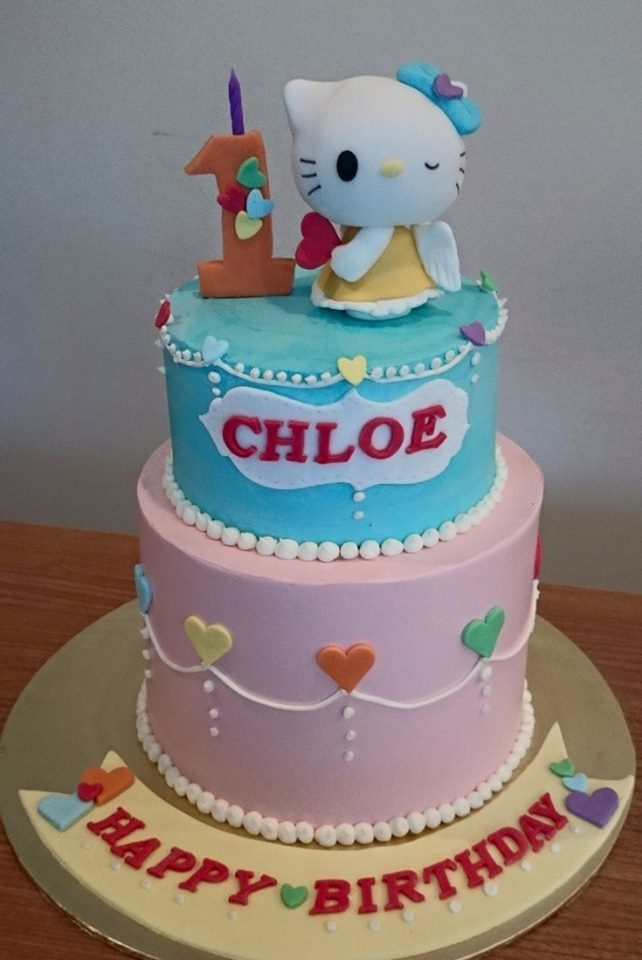 An angel Hello Kitty on top of a two-tiered cake, frosted with pink and blue buttercream. Made by: My Fat Lady Cakes and Bakes. Source