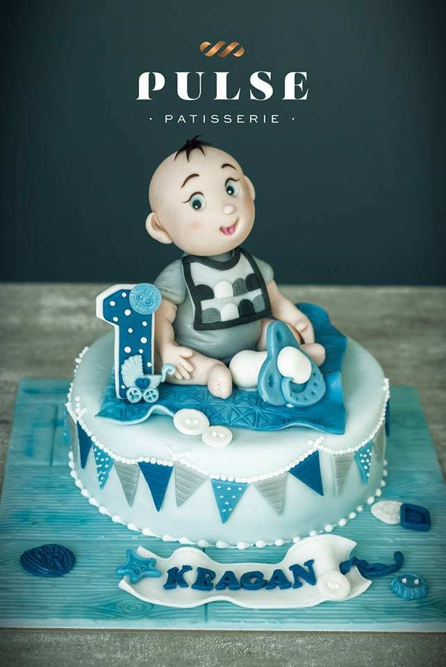 A round cake nicely wrapped with fondant and topped with a figurine of a baby boy. Made by: Pulse Patisserie Singapore - Recommend.sg