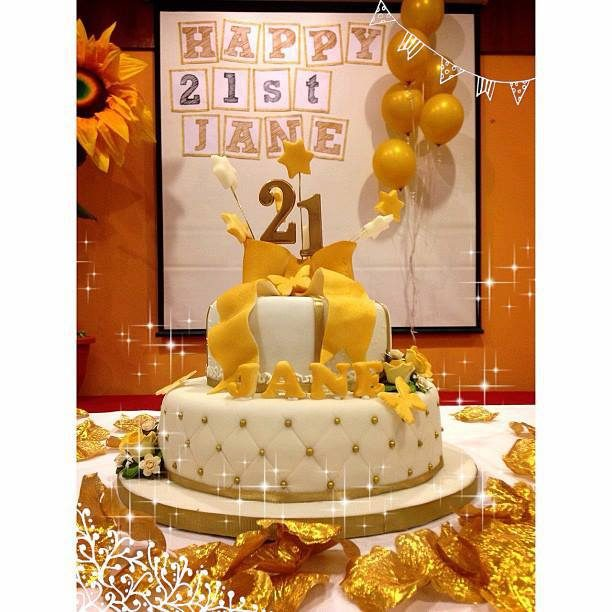 This two-tiered birthday cake looks perfect for this gold and white themed party. Made by: Temptations Cakes Singapore - Recommend.sg