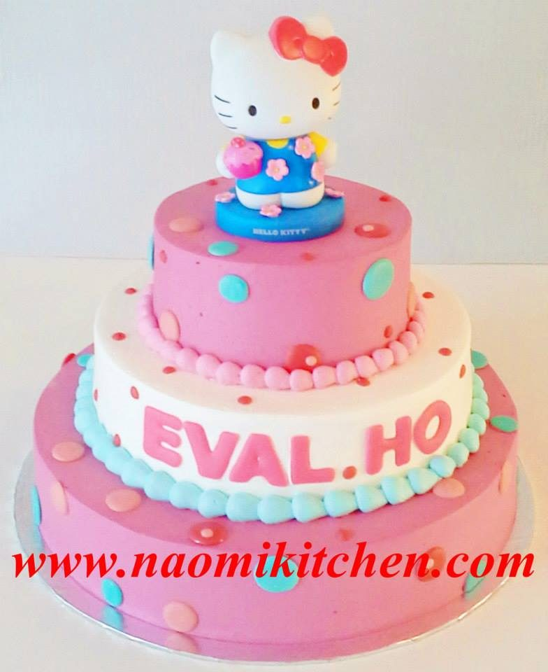 A three-tiered round cake with simple designs and a Hello Kitty topper. Made by: Naomi Kitchen. Source