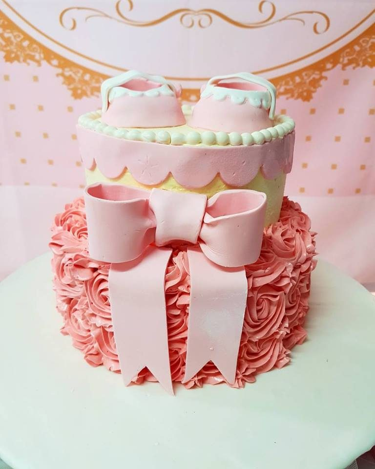 A two-tiered cake with a pair of pink booties. Made by: Little Sprinkles Singapore - Recommend.sg