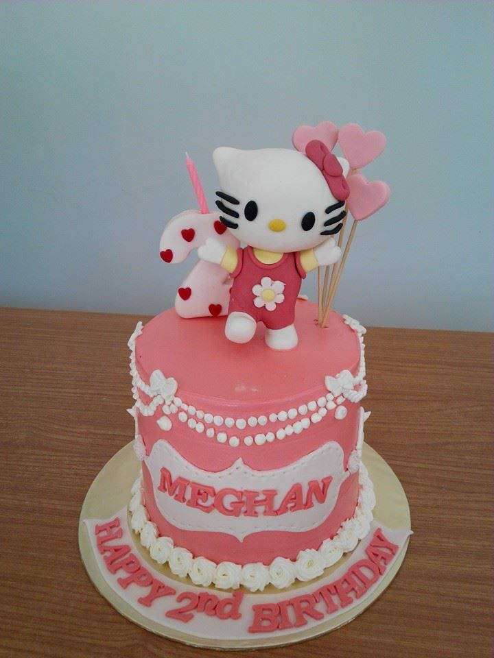 A pink and white themed tall round cake with Hello Kitty figure on top. Made by: My Fat Lady Cakes and Bakes. Source