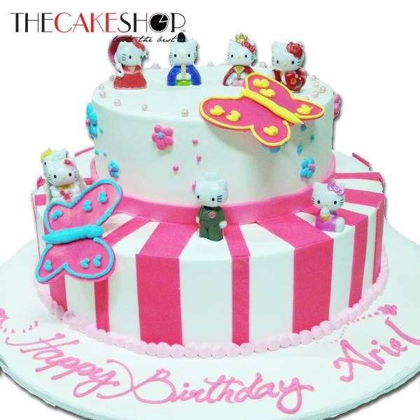 A Pink And White Cake With Hello Kitty Figures Made By The Shop
