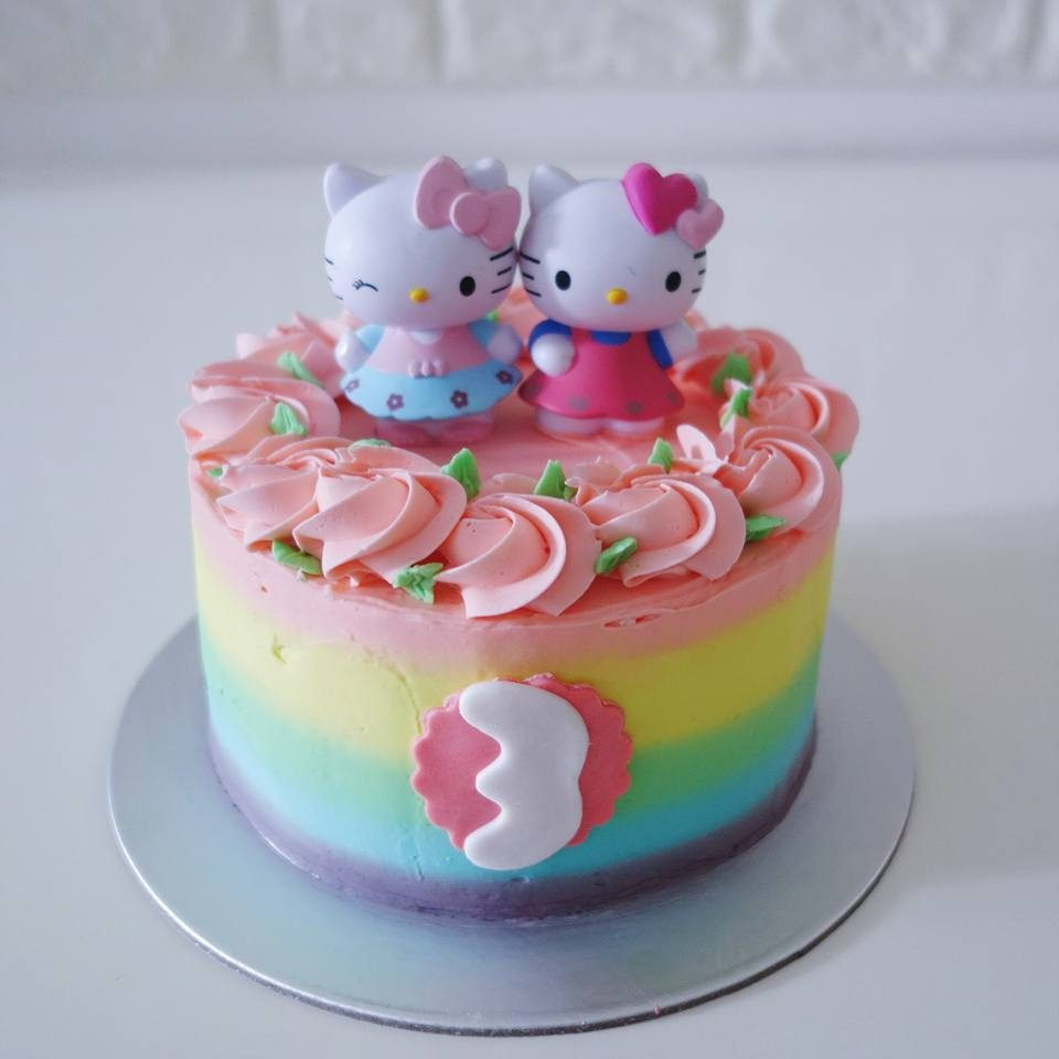 A tall round cake with rainbow buttercream frosting and Hello Kitty figures. Made by: River Ash Bakery. Source