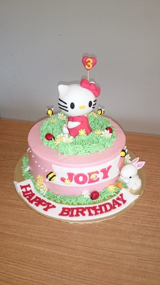 A Hello Kitty figurine on a round cake frosted and decorated with buttercream and other edible decorations. Made by: My Fat Lady Cakes and Bakes. Source