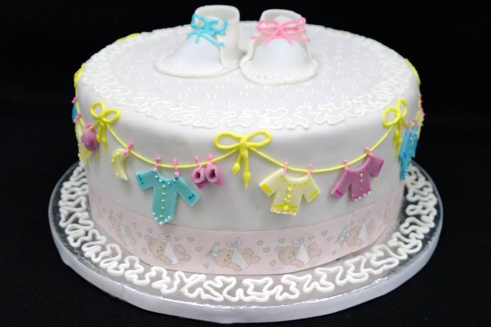 A white cake decorated with fondant cut outs and other simple decorations perfect for a baby shower. Made by: Temptations Cakes Singapore - Recommend.sg