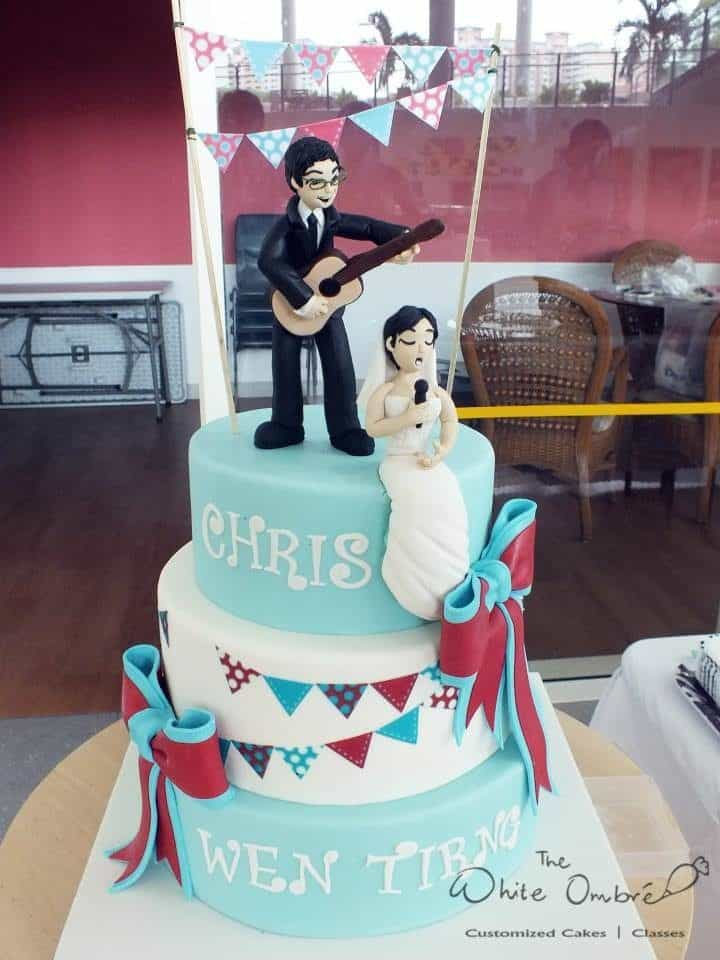 A modern pink and blue themed wedding cake with edible figurines of the bride and groom. Made by: The White Ombre.Source
