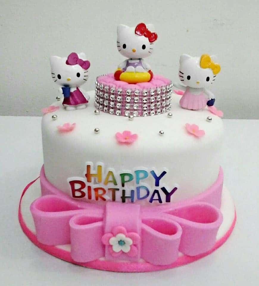 White and pink coloured round cake with three Hello Kitty figures on top. One of which, sits on a raised small piece of cake decorated with edible diamonds. Made by : Eats & Treats Bakery.Source