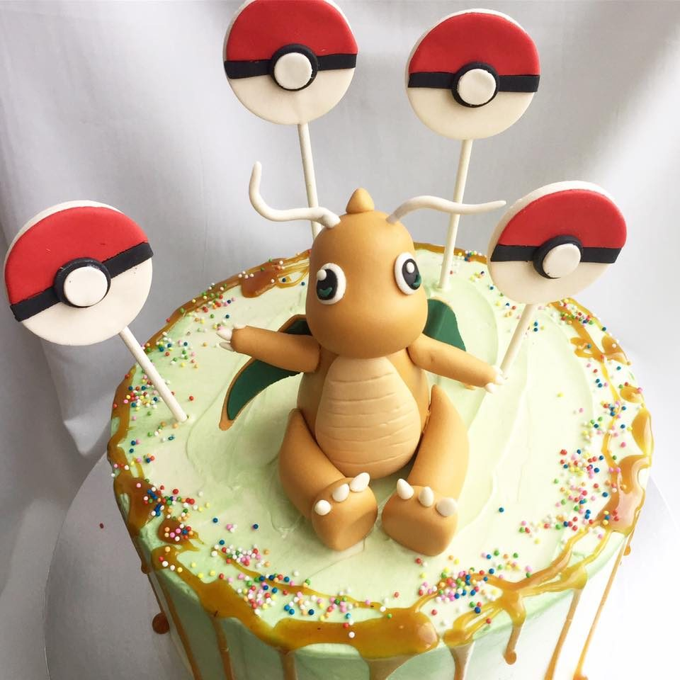 A round cake with caramel drip topped with edible Dragonite and Pokeball pops is simple but nice. Custom cake by Corine and Cake.Source