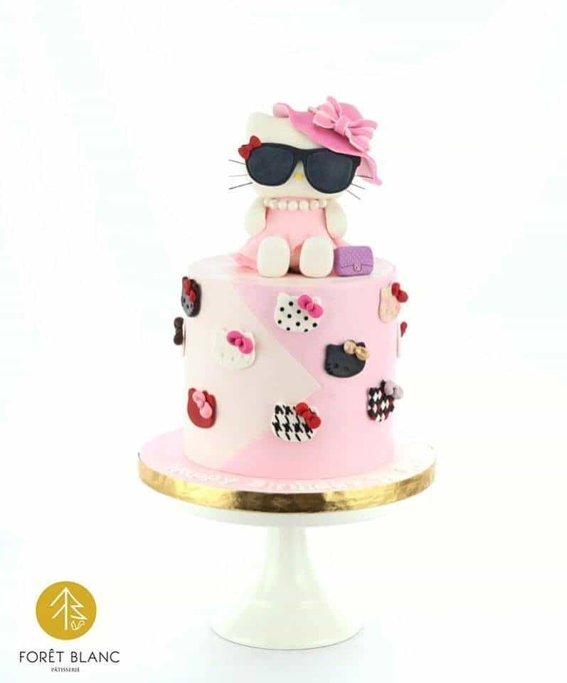A simple tall, round cake can stand out from the crowd with the addition of a Hello Kitty topper wearing a hat and a sunglasses. Made by: Foret Blanc Patisserie.Source