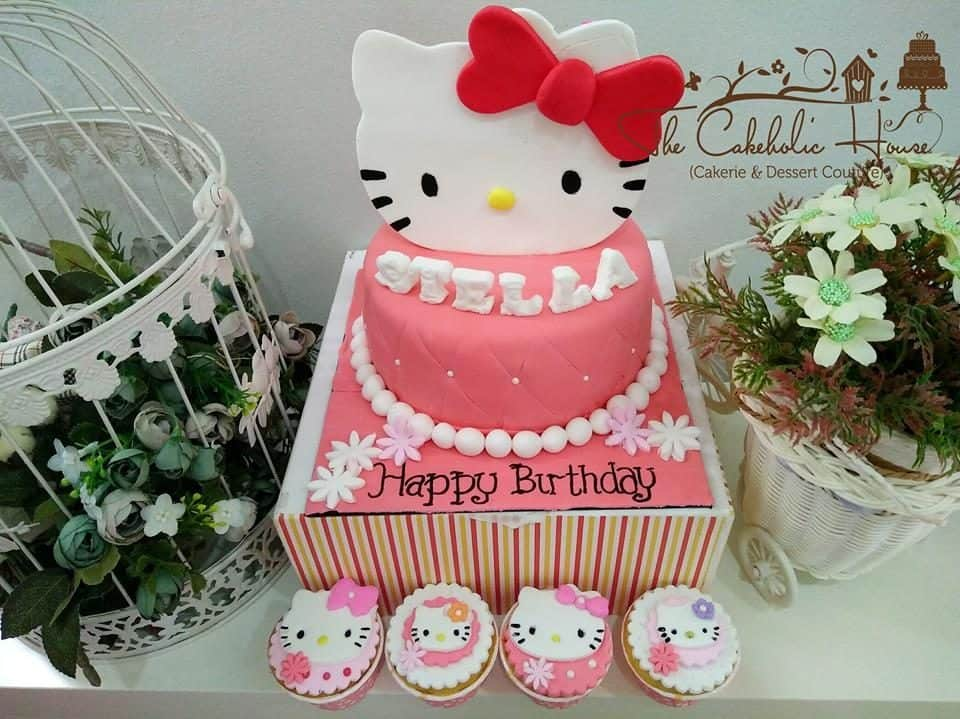 Cute cupcakes and a big round pink cake decorated with swiss dots, huge 2D Hello Kitty, and pearl candies sat on raised cake stand. Made by: The CakeHolic House. Source