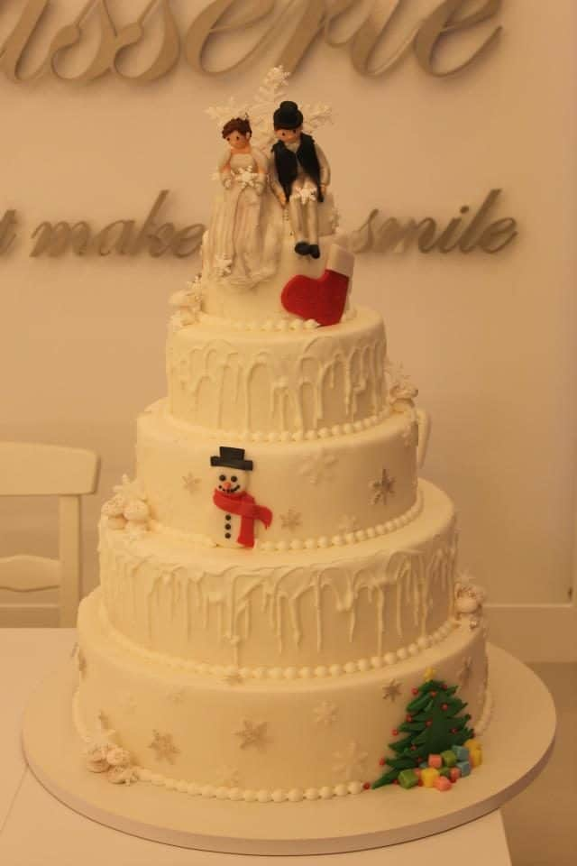 An all white wedding cake with Christmas themed decoration for a wedding held on Christmas day. Made by: Bonheur Patisserie.Source