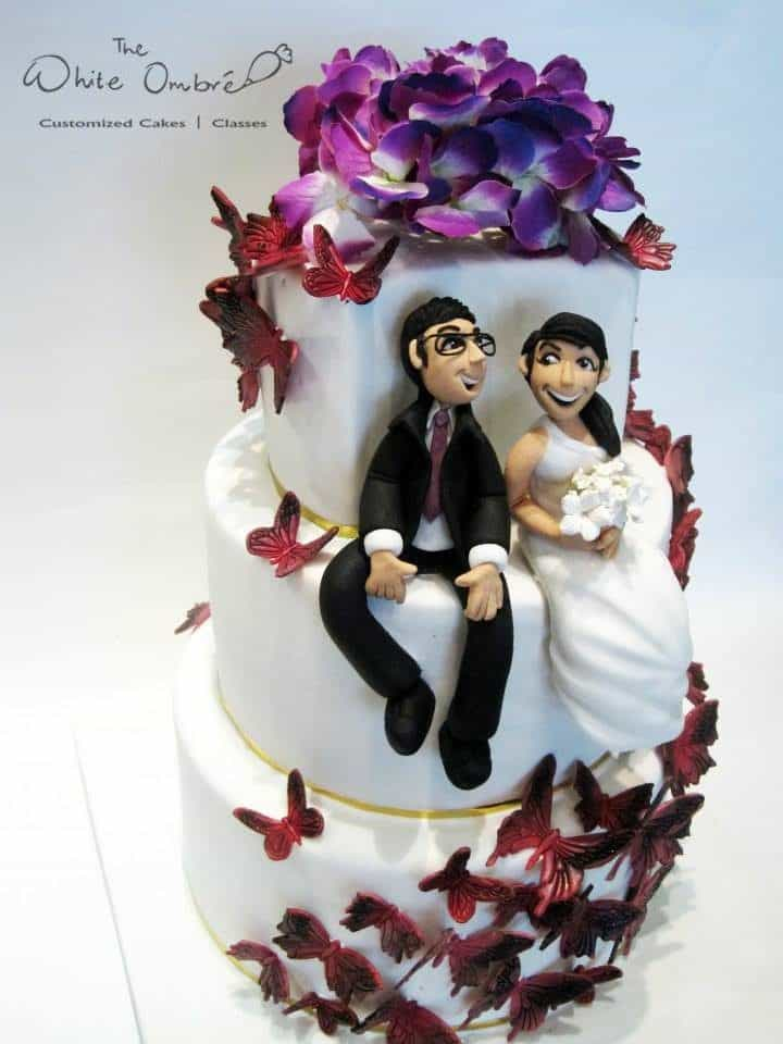 An all-white three-tiered cake decorated with cascading edible butterflies and fresh flowers on the top layer.Made by: The White Ombre.Source