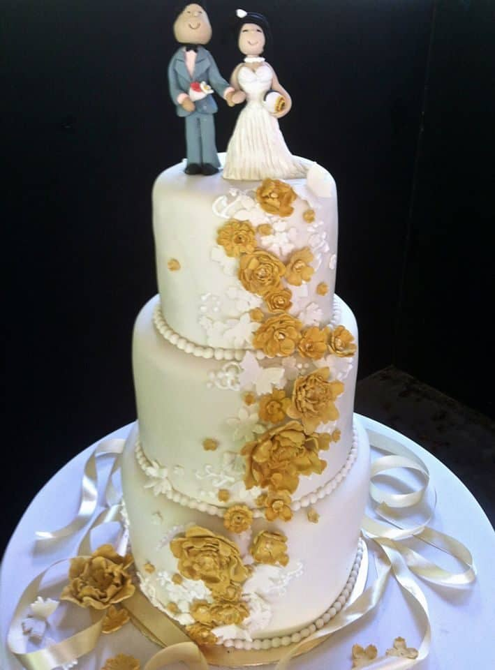 A three-tiered tall cake with white and gold cascading sugar flowers would look perfect for a cake cutting ceremony. Made by: My Fat Lady Cakes and Bakes. Source