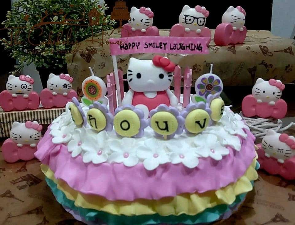 Round cake with three layered fondant icing and flower decoration on top, combined with a Hello Kitty topper.Made by: The CakeHolic House. Source