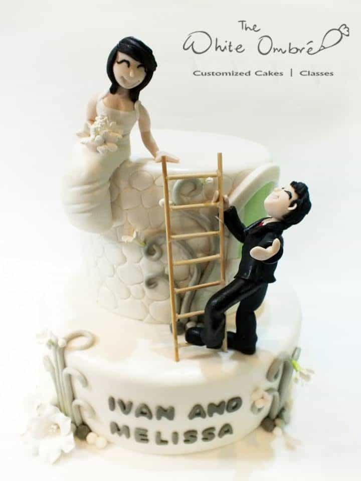A two-tiered round cake with fondant detailings and edible figurines of the bride and groom.Made by: The White Ombre.Source
