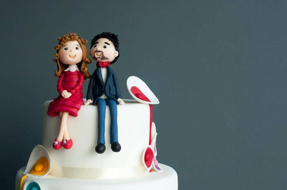A modern wedding cake with edible figurines in casual attire to resemble the couple. Made by: Pulse Patisserie.Source