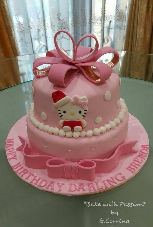 Two tiered cake decorated with ribbon, 2D Hello Kitty on the side, and white pearl icing. All made of fondants.Made by: Bake with Passion -by- G.Corrina. Source