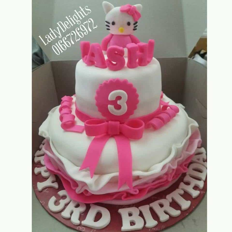 Two tiered birthday cake decorated with fondant ruffle and ribbon, plus a super cute Hello Kitty figure on top. Made by: Ladydelights Bakery .Source