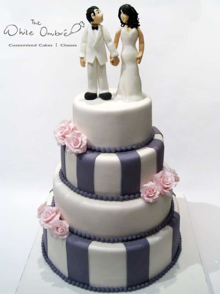 A modern four-tiered wedding cake design with grey stripes and pink sugar flowers.Made by: The White Ombre.Source