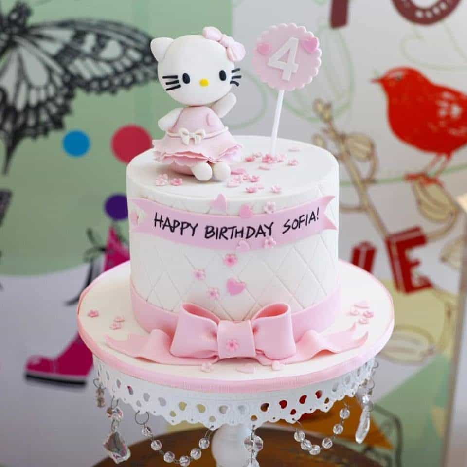 A single tier cake with swiss dots, small heart and flower shapes sprinkled over, with an addition of a Hello Kitty topper looks super cute and elegant at the same time. Made by: Little Collins.Source