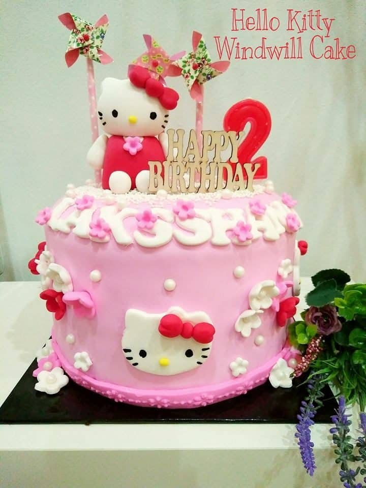 Hello Kitty with windmill toppers on top of a round, single tiered cake decorated with Hello Kitty and flower cutouts.Made by: The CakeHolic House. Source
