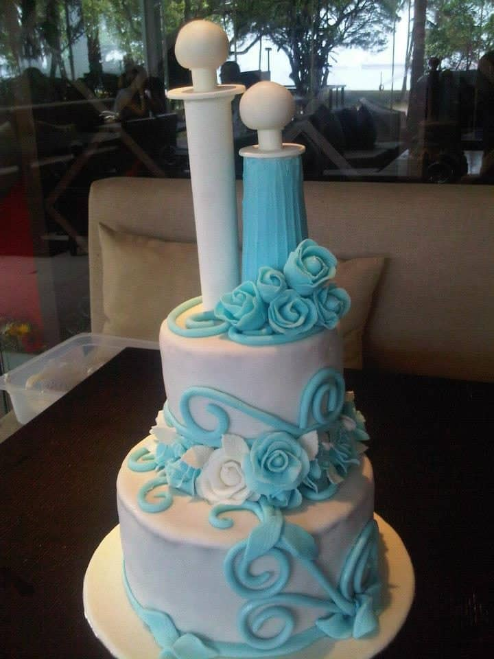 A two-tiered white cake with Tiffany blue and white sugar flowers.Made by: Bonheur Patisserie.Source