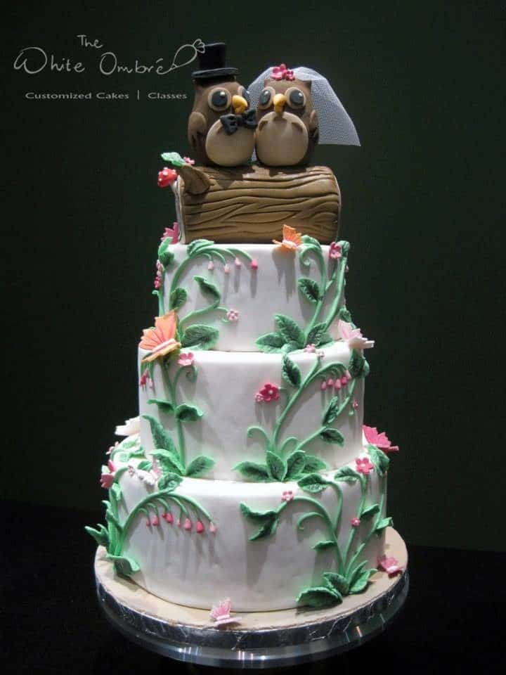 A three (or is it four?) tiered wedding cake with fondant detailings and love birds cake topper. Made by: The White Ombre.Source