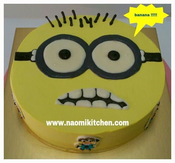 A regular round cake turned into the Minion's face with buttercream icing, and black and white fondant for the eyes, mouth and hair. Made by:Naomi Kitchen.Source