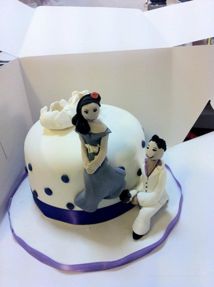 A simple white cake with purple detailings and figurines of the groom proposing the bride. Made by: My Fat Lady Cakes and Bakes.Source