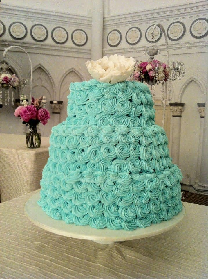 A three-tiered wedding cake with rosette buttercream frosting and peony sugar flower cake topper. Made by: My Fat Lady Cakes and Bakes.Source