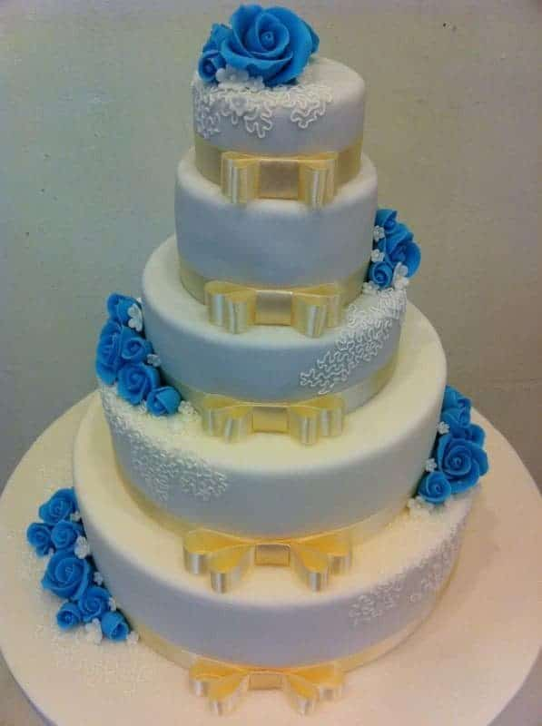 A five-tiered banded cake with blue sugar flowers and hand-drawn lace detailings. Made by: Bonheur Patisserie.Source