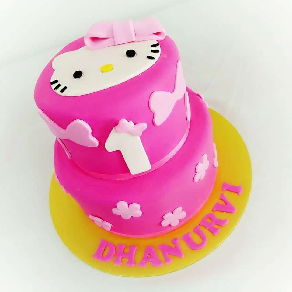 Two-tiered round pink cake with yellow base, ribbon and Hello Kitty fondant cutout sticked to the surface.Made by : Eats & Treats Bakery.Source