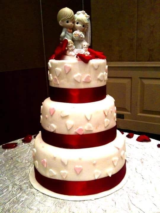 The cake artist keeps the three-tiered white cake simple with heart shaped cutouts and red ribbons. Made by: My Fat Lady Cakes and Bakes.Source