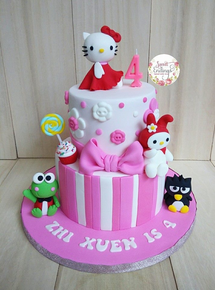 Two tiered cake with vertically-cut fondant covering for lower tier, and a white fondant icing for the upper tier, added with a cute-looking Hello Kitty figure on top, and other Sanrio figures below. We see Keroppi, Badtz-Maru, and My Melody! Made by: Sweet Endings.Source
