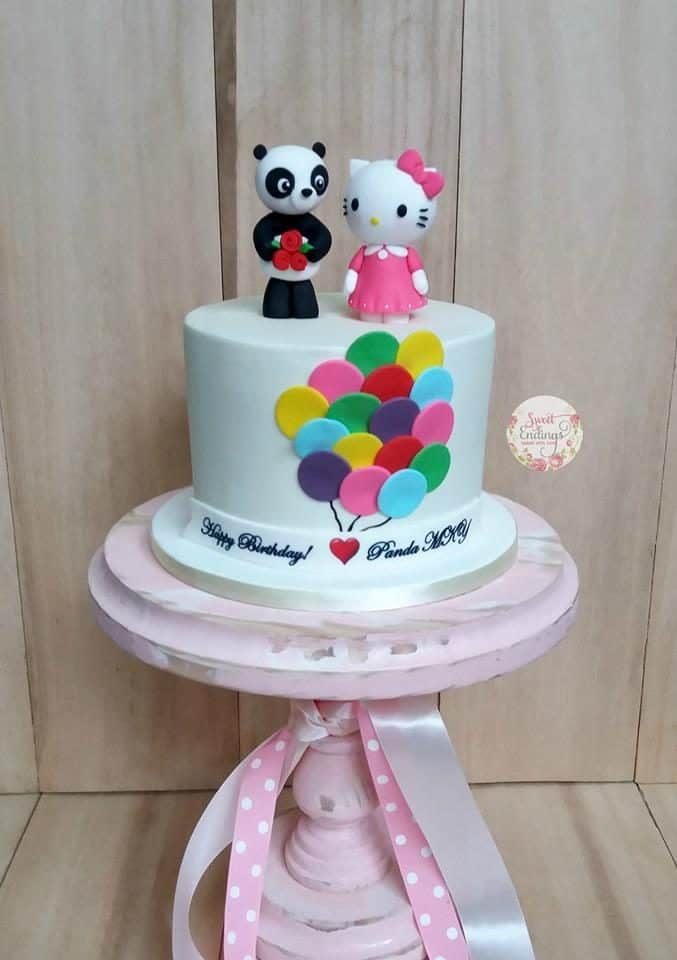 Instead of using other intricate shapes and details, this cake looks beautiful just by simple white fondant icing, balloon shaped fondant cut on the side, and a couple of Hello Kitty and panda toppers.. Made by: Sweet Endings.Source