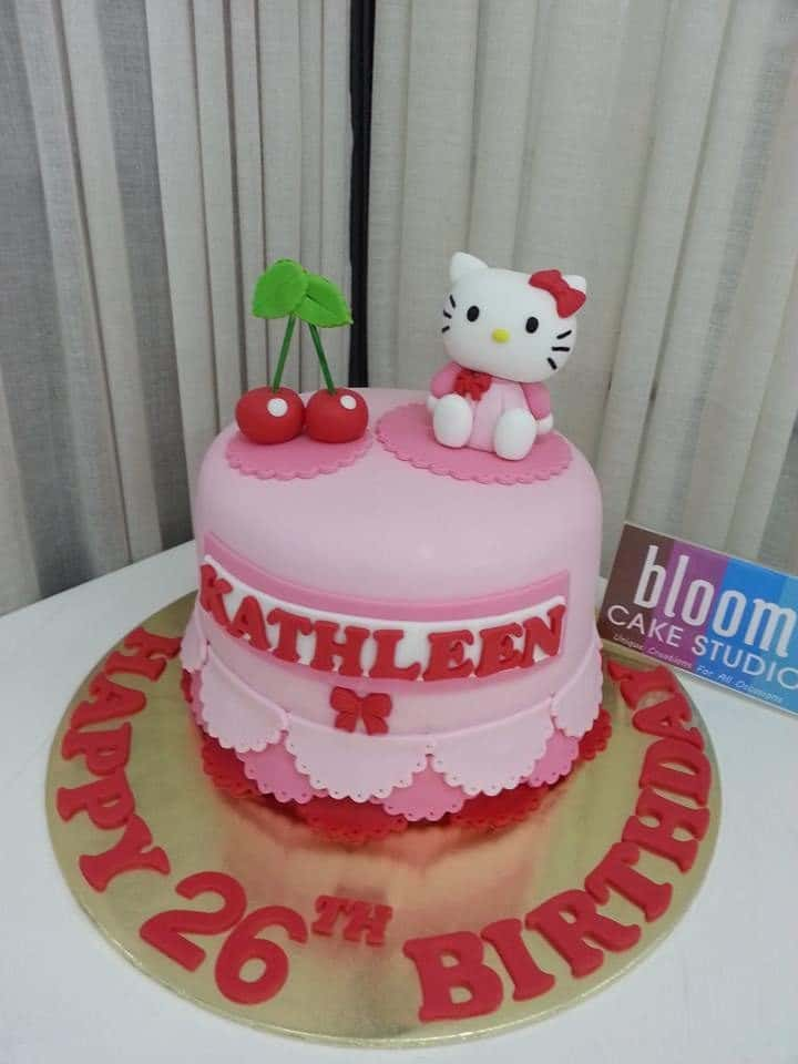 A simple round cake covered with fondant icing, arranged to look like drapery seems more interesting with a couple of cherries and a Hello Kitty fondant figure on top of it. Made by: Bloom Cake Studio.Source