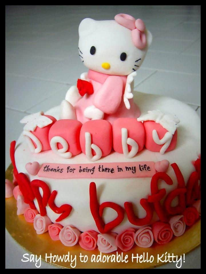 A small sized, round cake with, again, fondant icing is surrounded by small flower, and alphabet shaped fondant sculpted by hand, and a big angel Hello Kitty on top.. Made by: Leenie's Bakery.Source