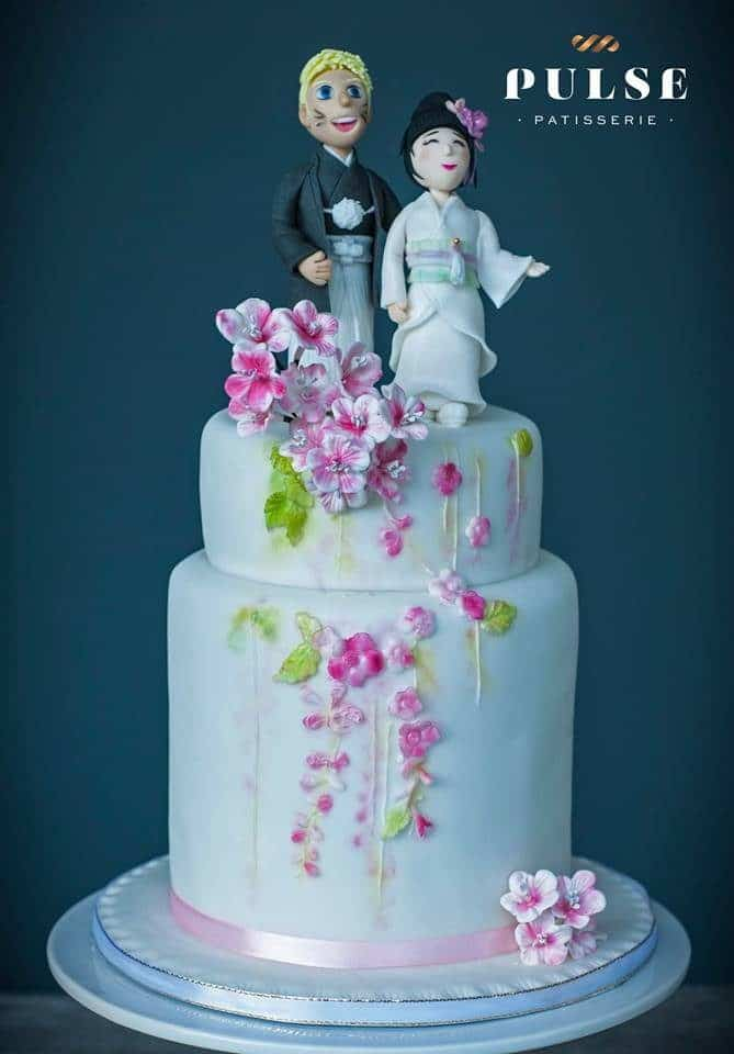 A Japanese themed singapore wedding cake with figurines of the bride and groom in Japanese traditional wear as the cake topper. Made by: Pulse Patisserie. Source
