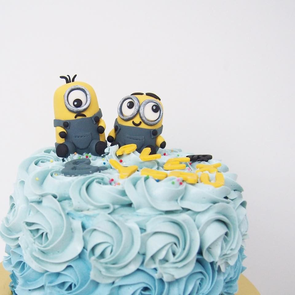 A round cake with blue rosette buttercream frosting with edible Minion figurines on top.Made by:Corine and Cake.Source