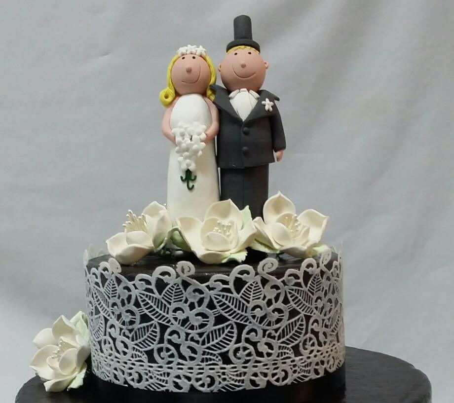 A black fondant cake with white lace detailings and handmade sugar flowers.Made by: Temptations Cakes.Source