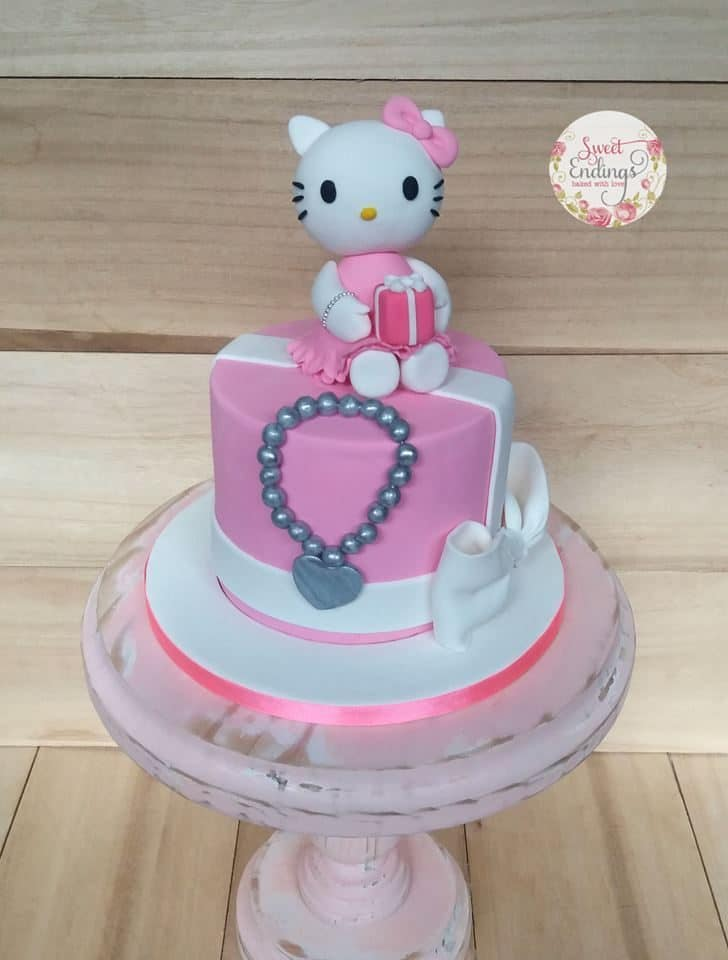 A simple, round cake with fondant icing, decorated with with a simple bow on the side, grey fondant shaped like a necklace, and a cute-looking Hello Kitty figure on top. Made by: Sweet Endings.Source
