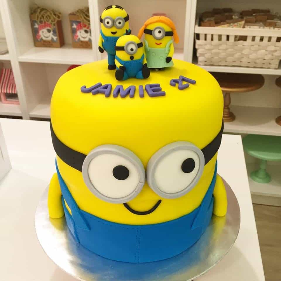 A tall round Minion shaped cake with three little Minion figurines as the cake topper.Made by:Little House of Dreams.Source