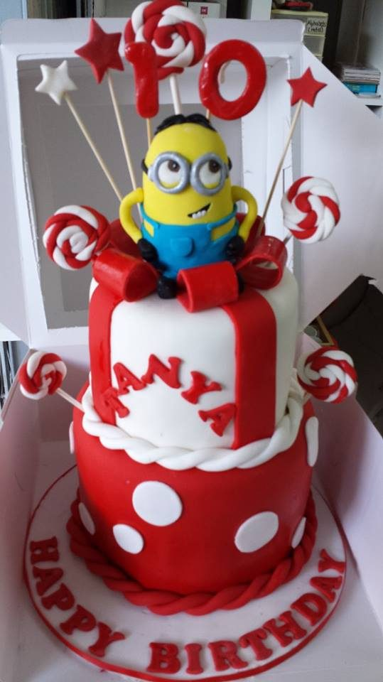 A two-tiered fondant cake with an edible Minion figurine on top.Made by:My Fat Lady Cakes and Bakes.Source